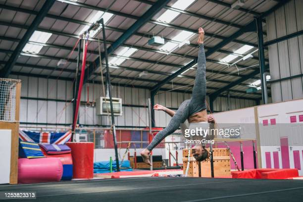 agile 30 year old female athlete practicing aerial cartwheel - legs apart stock pictures, royalty-free photos & images