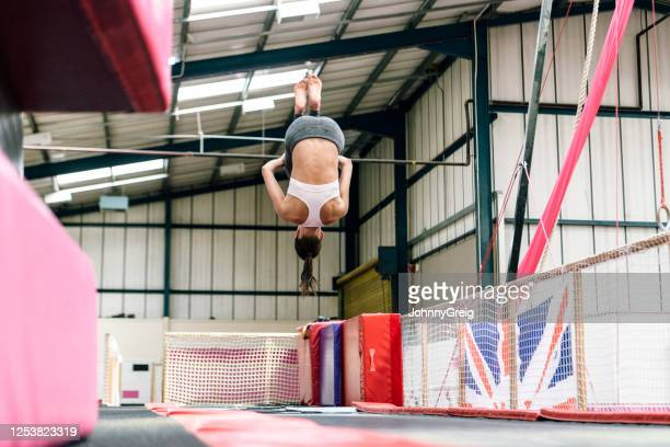 agile female gymnast in early 30s upside down in mid-air - floor gymnastics stock pictures, royalty-free photos & images