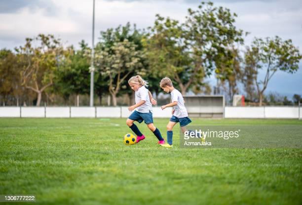 アジャイルガールサッカー選手は、練習で少年の前にドリブル - ドリブル ストックフォトと画像