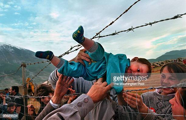 Agim Shala 2 years old is passed thru the barbed wire fence at the Arab camp as members of the Shala family are reunited after fleeing Kosovo The...