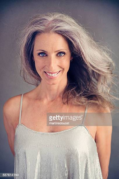 Aging gracefully, beautiful mature woman with silver hair and dress.