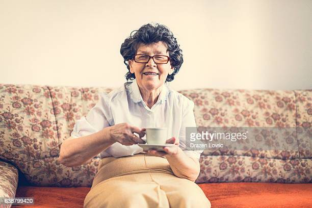 Aging with smile - senior woman drinking coffee
