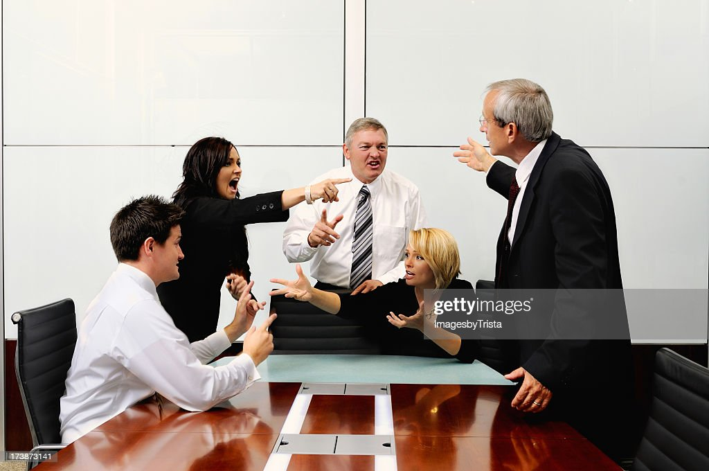 Agitated business people at a meeting pointing at each other : Stock Photo