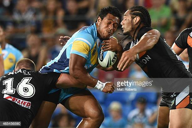 Agnatius Paasi of the Titans is tackled by Matthew Lodge and Martin Taupau of the Tigers during the round one NRL match between the Gold Coast Titans...