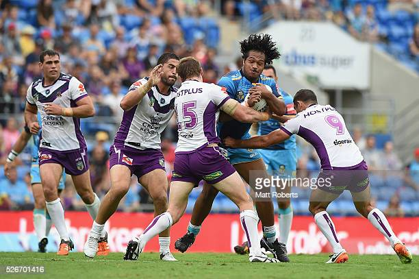 Agnatius Paasi of the Titans is tackled during the round nine NRL match between the Gold Coast Titans and the Melbourne Storm on May 1 2016 in Gold...