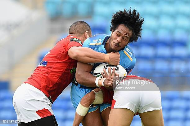 Agnatius Paasi of the Titans is tackled during the round seven NRL match between the Gold Coast Titans and the St George Illawarra Dragons at Cbus...