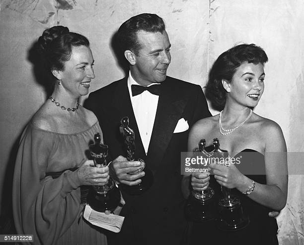 Agnes Moorehead and Dick Powell who presented Academy Awards and Jean Simmons who accepted the British Awards pose with the Academy Awards of Motion...