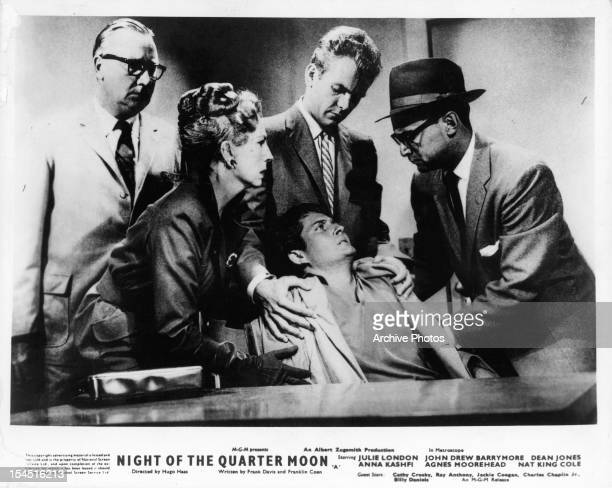 Agnes Moorehead Dean Jones and group standing over sitting man in a scene from the film 'Night Of The Quarter Moon' 1959