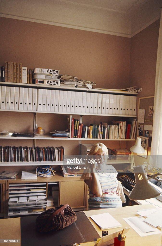 Agnetha Faltskog smiling, phoning an office base.