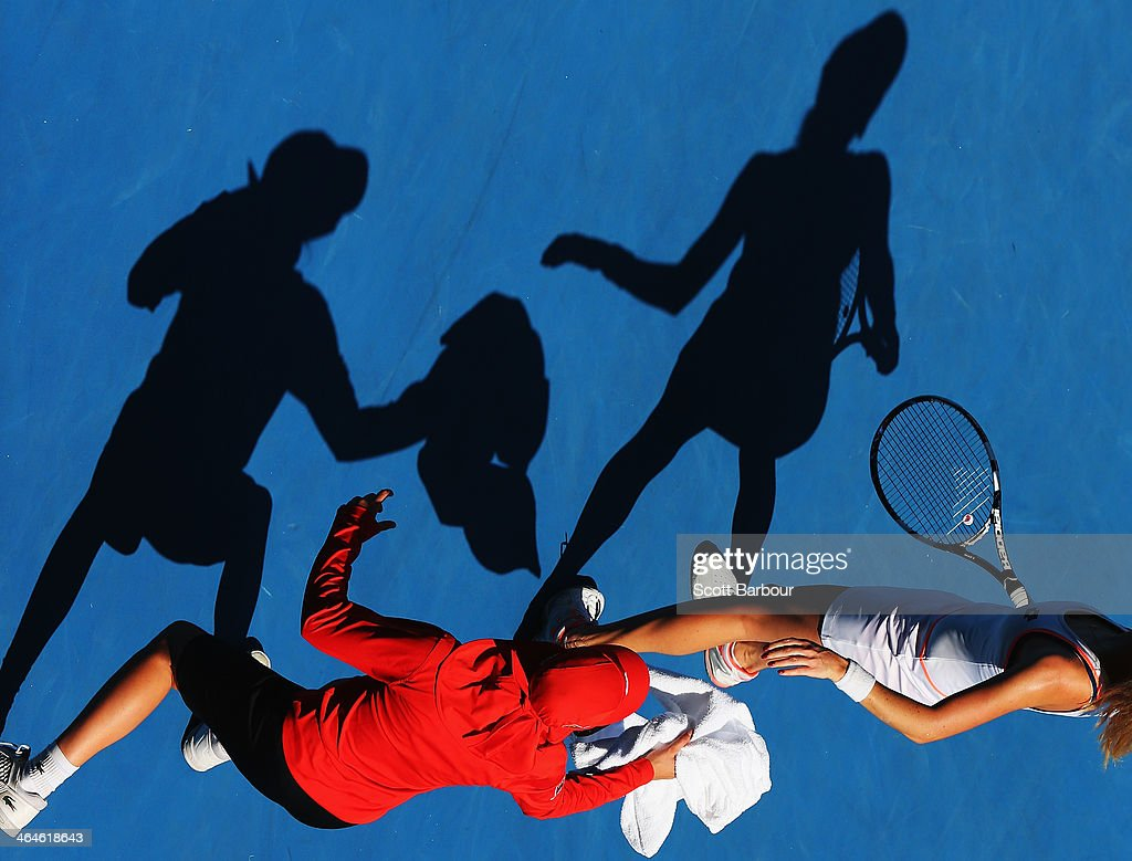 Agnieszka Radwanska of Poland is passed a towel by a ball kid in her semifinal match against Dominika Cibulkova of Slovakia during day 11 of the 2014 Australian Open at Melbourne Park on January 23, 2014 in Melbourne, Australia.