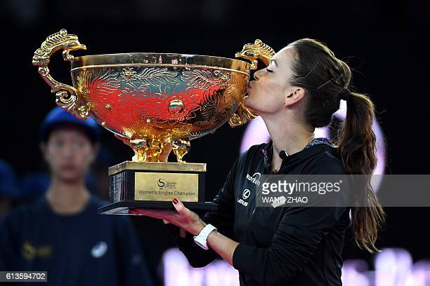 Agnieszka Radwanska of Poland kisses her trophy after beating Johanna Konta of Britain during the women's singles final of the China Open tennis...