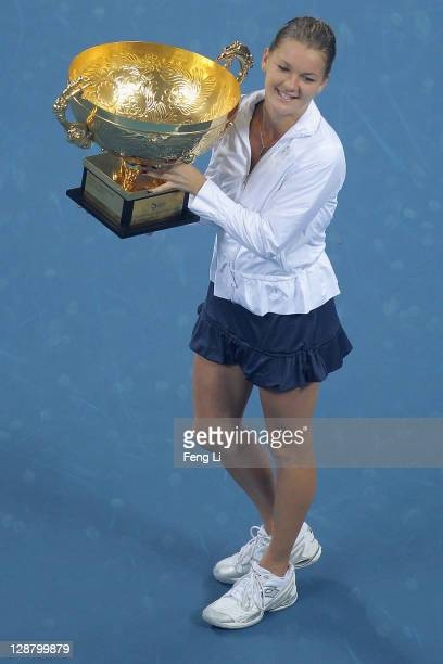Agnieszka Radwanska of Poland pose for photographers after winning against Andrea Petkovic of Germany in the women's final of the China Open at the...