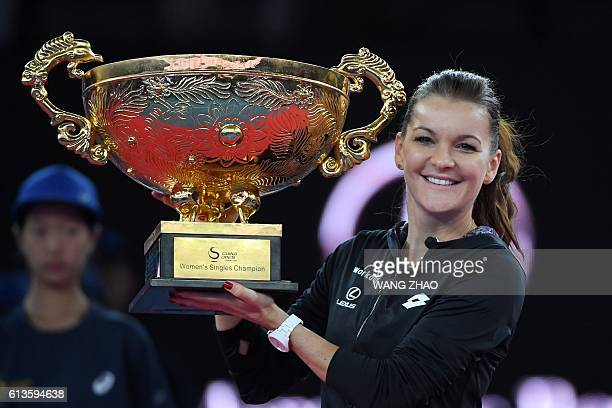 Agnieszka Radwanska of Poland poses with her trophy after beating Johanna Konta of Britain during the women's singles final of the China Open tennis...