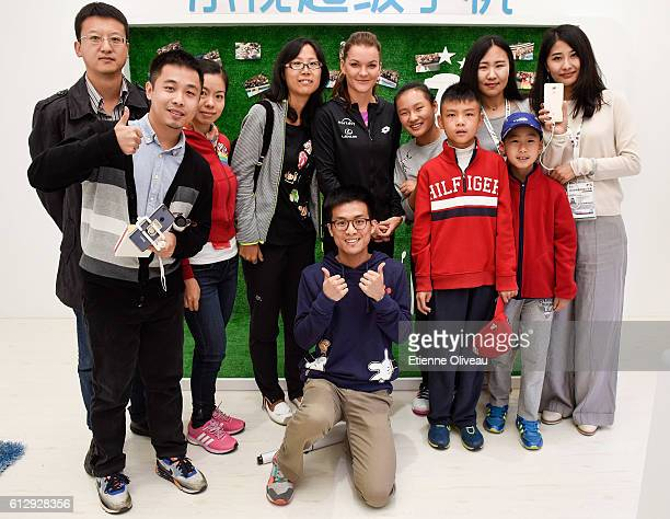 Agnieszka Radwanska of Poland poses with staff members at the LeMobile booth on day six of the 2016 China Open at the China National Tennis Centre on...