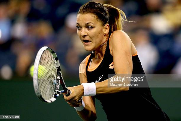 Agnieszka Radwanska of Poland returns a shot to Simona Halep of Romania during the semifinals of the BNP Parabas Open at the Indian Wells Tennis...