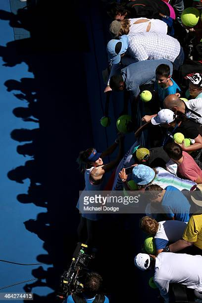 Agnieszka Radwanska of Poland signs autographs after winning her quarterfinal match against Victoria Azarenka of Belarus during day 10 of the 2014...