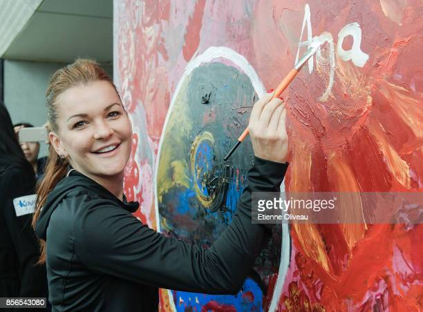 Agnieszka Radwanska of Poland signs her name on a painted wall during the Little Painter event on day three of the 2017 China Open at the China...