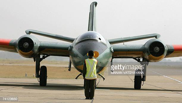 An Indian Air force official gives signals to the Canberra jet bomber during a ceremony to phase-out the Canberra bombers at the Air Force station in...