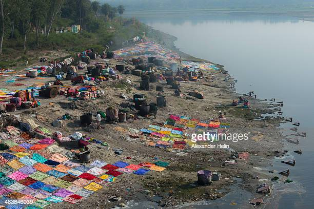 Agra, India - December 17 2013: Laundry workers washes and dries colorful clothes at the bank on Yamuna river in Agra.