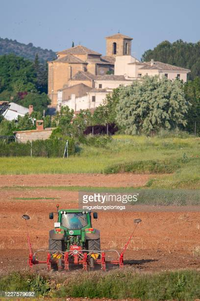 agrarian landscape, with a tractor in the foreground and the church of the village in the background - miguelangelortega fotografías e imágenes de stock