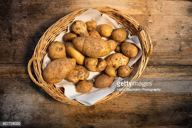 agria potatoes in a basket on a weathered garden table - heinz baumann photography stock-fotos und bilder