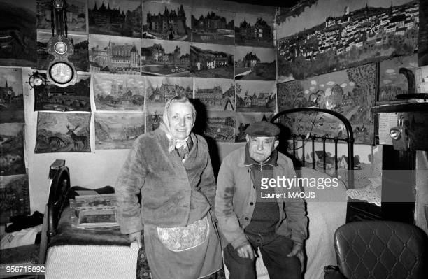 L'agriculteur Gaston Duchamp ici avec sa femme Yvonne entouré de dizaines de tableaux naïfs qu'il a peints tout au long de sa vie en décembre 1981...