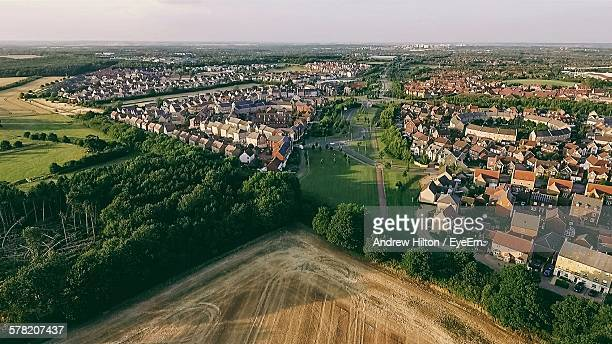 agricultural field by town against sky - milton keynes stock pictures, royalty-free photos & images