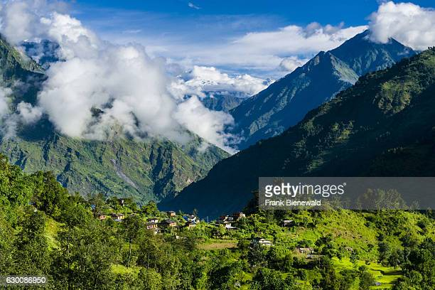 Agricultural landscape with green terrace rice fields and the houses of the village in Upper Kali Gandaki valley looking towards Mustang