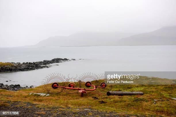 agricultural machine at seaside of breiddalsvik, eastern iceland - austurland stock-fotos und bilder