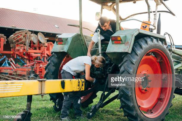 agricultural occupation: two farmers repairing a trailer on a tractor - repairing stock pictures, royalty-free photos & images