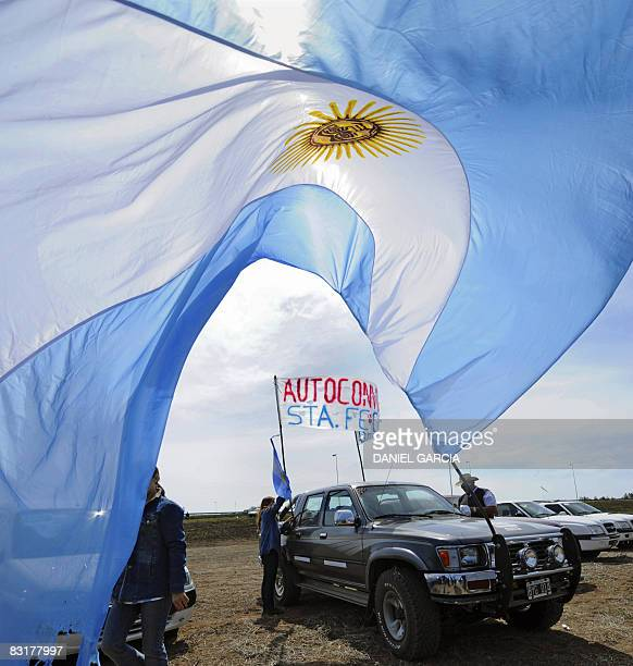 Agricultural producers put a banner on a vehicle during the protest on a road junction in the town of San Pedro 160 km northwest of Buenos Aires amid...