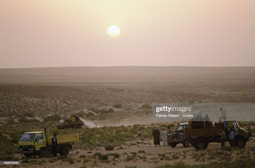 Agricultural vehicles spray pesticide over the land after a swarm of desert locusts invaded the Lagahout region of Algeria. The invasion of locusts in Algeria, and throughout Africa, drastically reduced food production, forcing the government to provide food aid programs and emergency assistance to rural communities.