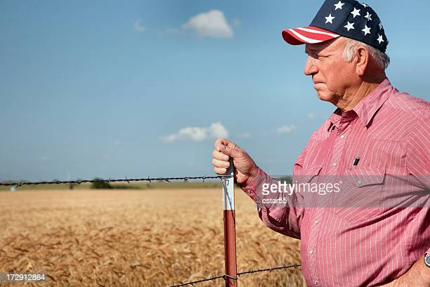 Agriculture: American Farmer or rancher by fence and wheat field