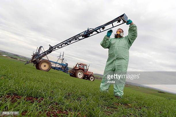 Agriculture Farmer in a field with his crop duster wearing safety clothes Here checking and unblocking a nozzle