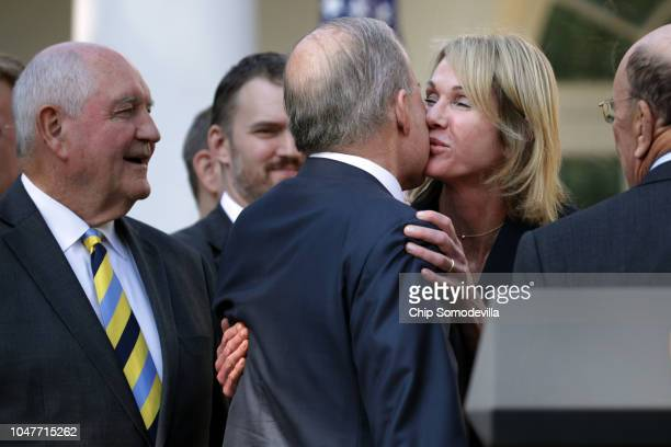Agriculture Secretary Sonny Perdue looks on as Director of the National Economic Council Larry Kudlow kisses US Ambassador to Canada Kelly Craft...
