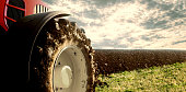 Agriculture. Tractor plowing field. Wheels covered in mud, field in the background. Cultivated field. Agronomy, farming, husbandry concept.