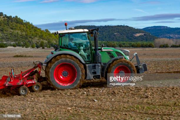 agriculture - tractor plowing the field - tiller stock photos and pictures