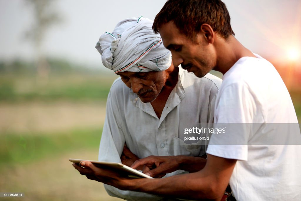 Agronomist consulting with farmer outdoor in the field : Stock Photo