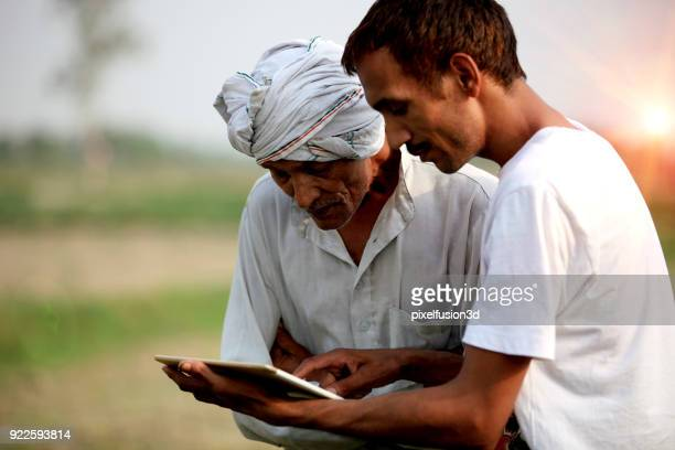 agronomist consulting with farmer outdoor in the field - indian subcontinent ethnicity stock pictures, royalty-free photos & images