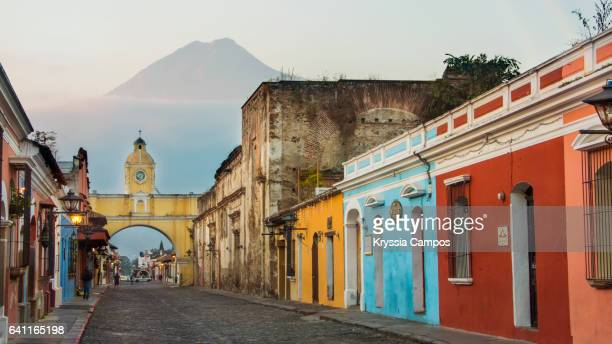 agua volcano and arco de santa catalina (santa catalina arch) in antigua guatemala - guatemala stock pictures, royalty-free photos & images