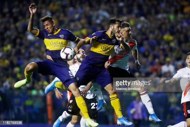 Agustin Almendra and Emmanuel Mas of Boca Juniors jump for the ball as he plays a handball during the Semifinal second leg match between Boca Juniors...