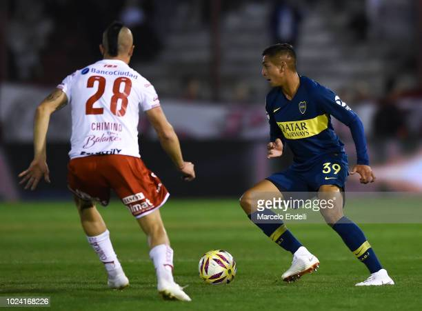 Agustin Almendra of Boca Juniors drives the ball against Christian Chimino of Huracan during a match between Huracan and Boca Juniors as part of...