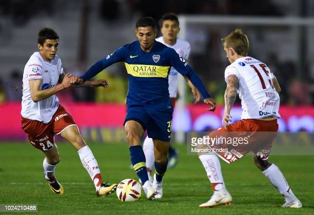 Agustin Almendra of Boca Juniors fights for the ball with Carlos Araujo and Ivan Rossi of Huracan during a match between Huracan and Boca Juniors as...