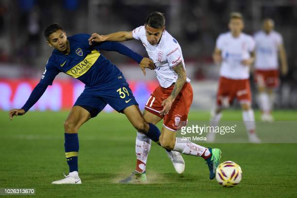 Agustin Almendra of Boca Juniors fights for the ball with Carlos Auzqui of Huracan during a match between Huracan and Boca Juniors as part of...
