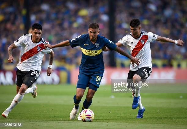 Agustin Almendra of Boca Juniors fights for the ball with Enzo Perez and Exequiel Palacios of River Plate during a match between Boca Juniors and...
