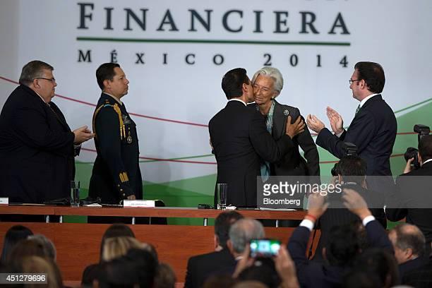 Agustin Carstens governor of Banco de Mexico left and Luis Videgaray Mexico's finance minister right applaud as Enrique Pena Nieto Mexico's president...