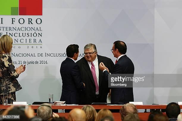 Agustin Carstens governor of Mexico's central bank Banco de Mexico center shakes hands with Enrique Pena Nieto Mexico's president second left as...