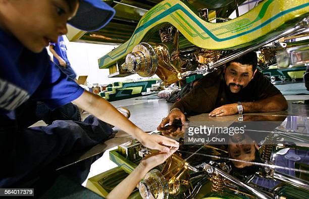 Agustin Castaneda left lends a hand as Alejandro 'Chino' Vega sets up the display for his 1979 Chevrolet Monte Carlo on Saturday October 7 2006 at...