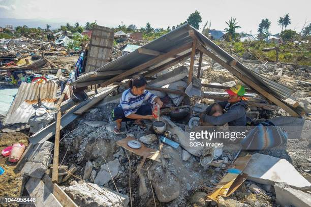 Agustin cooks for her husband Baktiar between the ruins of his house in Balaroa village after the earthquake in Palu A deadly earthquake measuring 77...