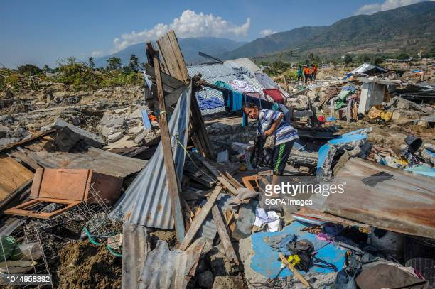 Agustin looking for items left in the ruins of her house in Balaroa village after the earthquake in Palu A deadly earthquake measuring 77 magnitude...